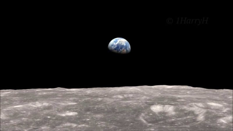 Half of the Earth is floating in the black sky over the gray moon's cratered surface.