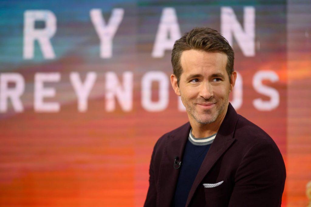Ryan Reynolds draagt een zwart T-shirt met een kastanjebruin jasje dat tegen een rood-blauwe achtergrond staat met zijn naam in het wit achter hem geschreven.